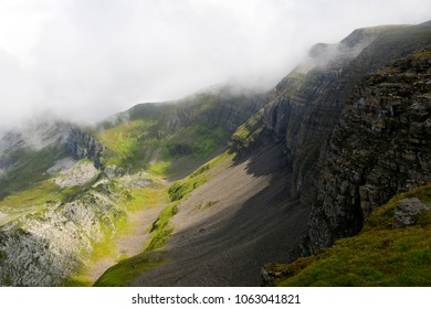 A green valley with a large rockface in the clouds