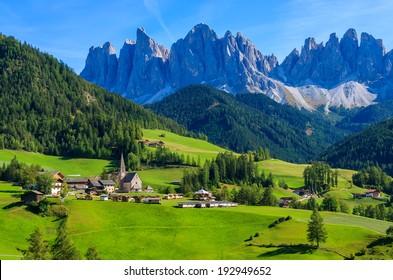 Green valley Santa Maddalena village church, Val di Funes, Dolomiti Mountains, Italy