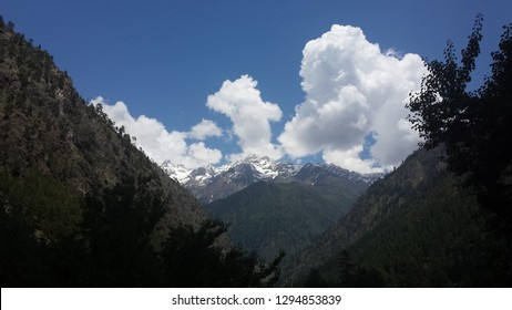 Green valley with snow capped mountains in the horizon, shot from Kasol, Parvati Valley, Himachal Pradesh, India