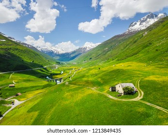 Green valley with yellow dandelions with snow covered mountain in the background at Andermatt