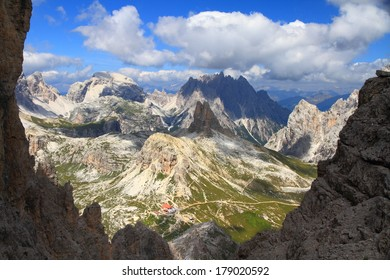 Green valleys and eroded mountains in the background, Dolomite Alps, Italy