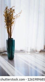 Green vase with dried flower. Placed in front of white curtains. There is a light and shadow of sunlight. The interior is beautiful, smooth, luxury, minimal style.