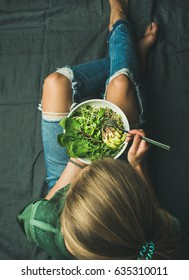 Green vegan breakfast meal in bowl with spinach, arugula, avocado, seeds and sprouts. Girl in jeans holding fork with knees and hands visible, top view. Clean eating, dieting, vegetarian food concept
