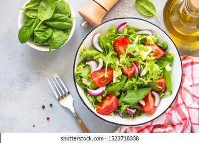 Green vegan salad from green leaves mix and vegetables. Top view on gray stone table. - Shutterstock ID 1523718338