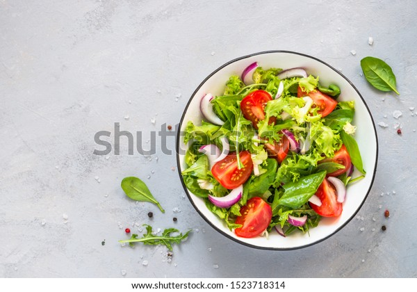 Green vegan salad from green leaves mix and vegetables. Top view on gray stone table.
