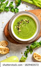 Green vegetable cream soup in a white bowl on a gray concrete background top view. Vegan soup puree of green vegetables. Vegetarian and diet food.