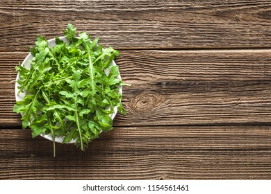Green vegetable, leaves of arugula on plate on wooden table, healthy food concept