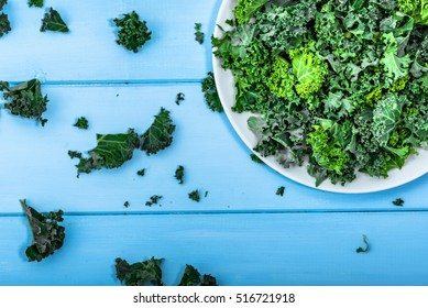 Green vegetable, leaves of kale from above on white plate, vegetarian food concept