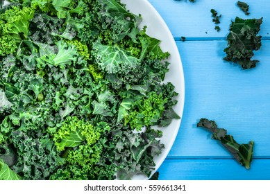 Green vegetable, leaves of kale, close view on plate on blue table, healthy eating concept