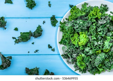 Green vegetable, leaves of kale, overhead on white plate, healthy eating, vegetarian food concepts