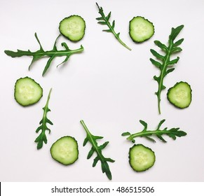 Green vegetable organic pattern with cucumbers and rocket salad. Flat lay on white table, top view