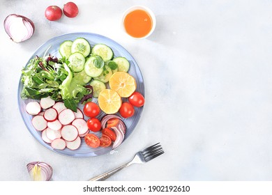 Green vegetable salad with cherry tomatoes, cucumber, radish and fresh arugula, detox diet. Healthy natural breakfast for weight loss, cholesterol and GMO free, selective focus, rustic style