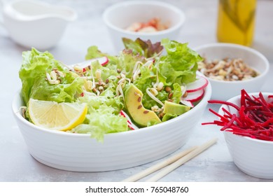 Green vegetable salad with sprouts, beetroot and hummus. Healthy detox vegan food concept.