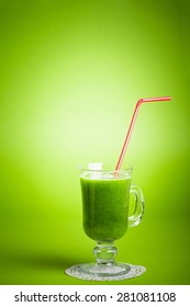 Green vegetable smoothie juice against green background with red drinking straw