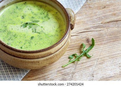 green vegetable soup with broccoli, rucola and spinach in a brown  bowl on a rustic wooden board