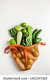 Green vegetables and fruits in orange string bag on white background. Zucchini, cucumber, pepper, avocado, celery, spinach, lime. The view from the top. Isolated from the space mine. No plastic.