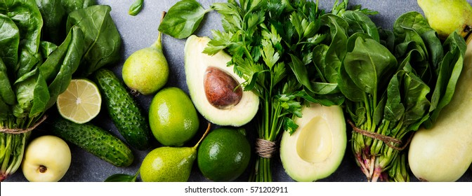 Green vegetables and herbs assortment on a grey stone background. Top view