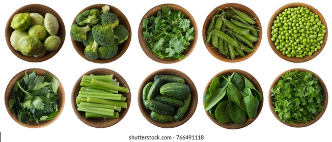 Green vegetables and herbs isolated on a white background. Squash, brocoli, green peas, cucumbers and leaves parsley, celery, cilantro, spinach in wooden bowl with copy space for text. Top view.