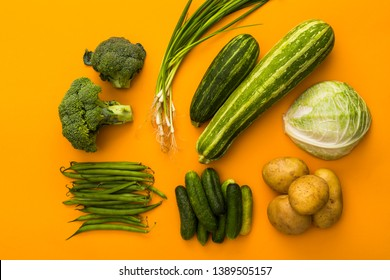 green vegetables on yellow background colorful concept, top view, potatoes, broccoli, cucumber, onion, cabbage, zucchini, beans