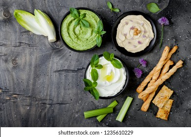 Green vegetables raw snack board with various dips. Yogurt sauce or labneh, hummus, herb hummus or pesto with crackers, grissini bread and fresh vegetables. Middle eastern meze snacks set