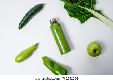 Green vegetables and smoothies in a plastic bottle on a white background. Healthy concept. Top view, Space for text