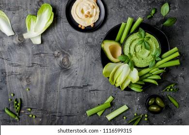 Green vegetables snack board with various dips. Hummus, herb hummus or pesto with fresh vegetables. Healthy raw summer vegan platter. Copy space