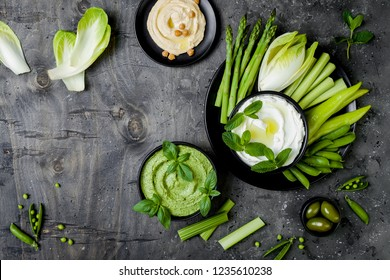 Green vegetables snack board with various dips. Yogurt sauce or labneh, hummus, herb hummus or pesto with fresh vegetables. Healthy raw summer vegan platter. Copy space