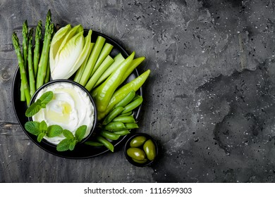 Green vegetables snack board with yogurt sauce or labneh dip. Healthy raw summer platter. Copy space