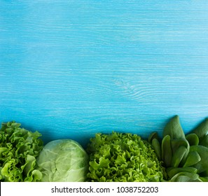 Green vegetables. Green vegetable on blue wooden background. Spinach, lettuce and cabbage. Top view. Vegetables at border of image with copy space for text.
