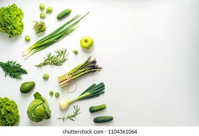Green vegetables wide flat lay concept. Microgreens, brussels sprouts, asparagus, rosemary, avocado, onion, cabbage and cucumber on white background, top view