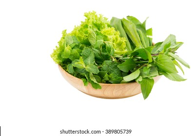 Green vegetables in wooden plate  on white isolated background. Selective focus.