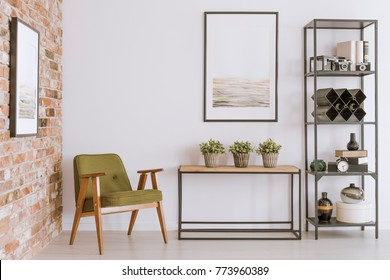 Green vintage chair next to a table with plants in living room with painting on wall