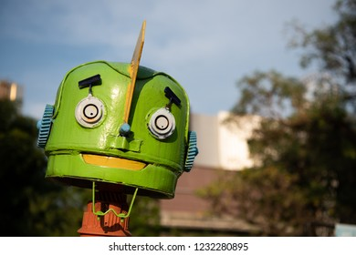 Green vintage classic funny steel robot head on the metro town background,close up picture.