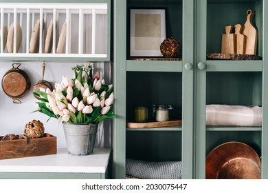 Green vintage cupboard with glass doors, set of various sized wooden cutting boards and tablecloths, countertop with white surface, lots of flowers in metal bucket, comfortable kitchen enviroment