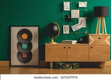 Green vintage leather bag under a retro dresser with hipster decorations and a tripod desk lamp in a student's bedroom interior