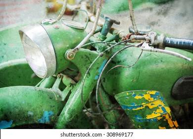 Green vintage motorbike headlamp. Textured image