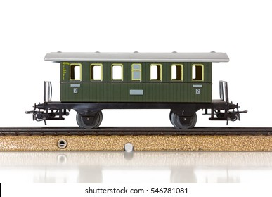 Green vintage passenger car of a model electric train on the rails