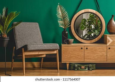 Green vintage room interior with plants, mirror, chair, wooden cabinet and floor concept
