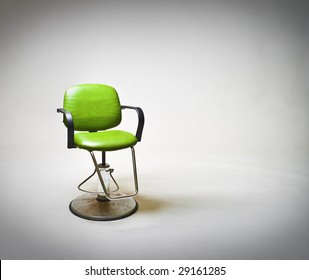 Green vintage vinyl covered barbershop or beauty salon chair against large white backdrop. Lots of copy space to right.