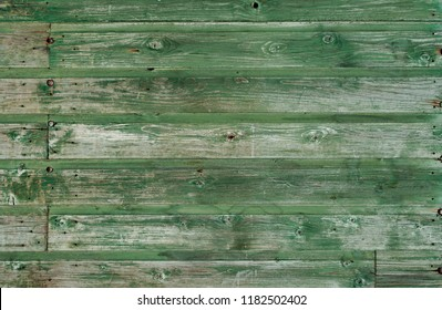 green vintage weathered wooden fence with rusty nails