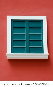 green vintage window on red wall