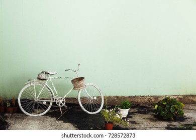 Green wall background with white vintage bicycle