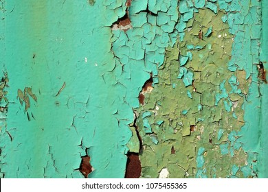 Green wall with peeled paint close up