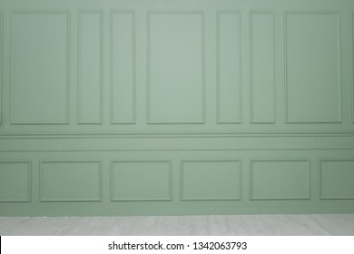A green wall with wainscoting background