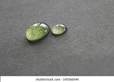 green water droplets on grey background