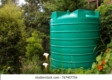Green water tank in a garden setting with flowers in the foreground