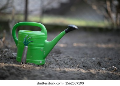 Green watering can and garden accessories on the patch during springtime cleaning in the garden.