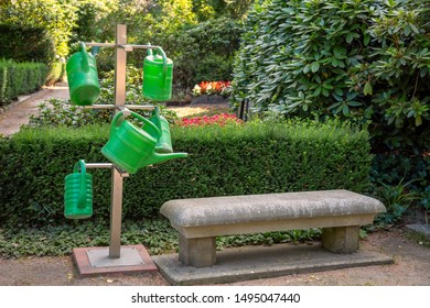 Green watering cans on a stand with a stone bench