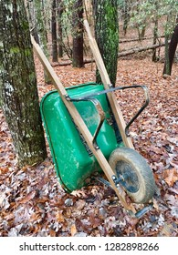 A green wheelbarrow in the woods propped against a tree, surrounded by leaves, concept for fall yard work.