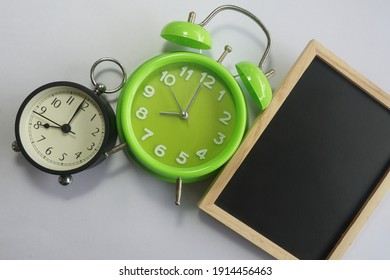 green and white alarm clock on white background